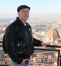 Photo of Glennon with an expansive shot of Florence, Italy, behind him.