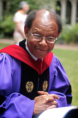 James Cone outside in graduation regalia