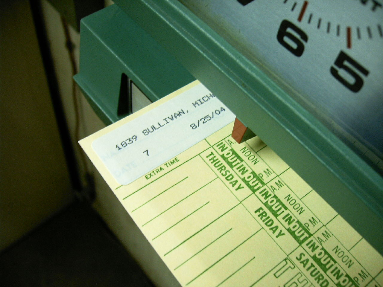 image of a worker's time card being punched