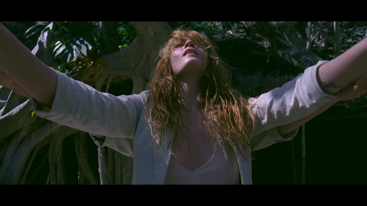 "Still from Florence + the Machine's music video, ""How Big How Blue How Beautiful."" Florence Welch in white raising hands to sky."