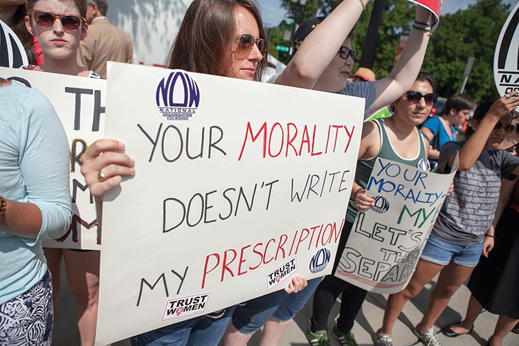 "photo taken at a Washington, DC protest during the Supreme Court's hearing of Burwell v. Hobby Lobby (2014). A protestor holds a sign, ""Your morality doesn't write my prescription."""