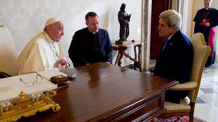 Former US Secretary of State John Kerry sits with Pope Francis and his translator on December 2, 2016 in the Vatican. They sit around Pope Francis' desk.