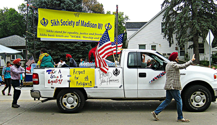 "A white truck in a middle of a parade carries a yellow sign in its bed that reads ""Sikh Society of Madison WI."" Two American flags are on each side of the sign. A Sikh man wearing a dastar (turban) walks next to the truck and waves to the crowd"