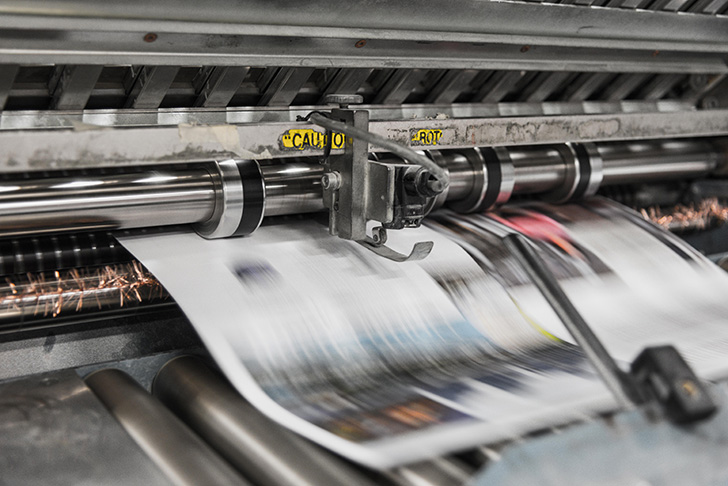 Two newspaper are being printed on a modern press