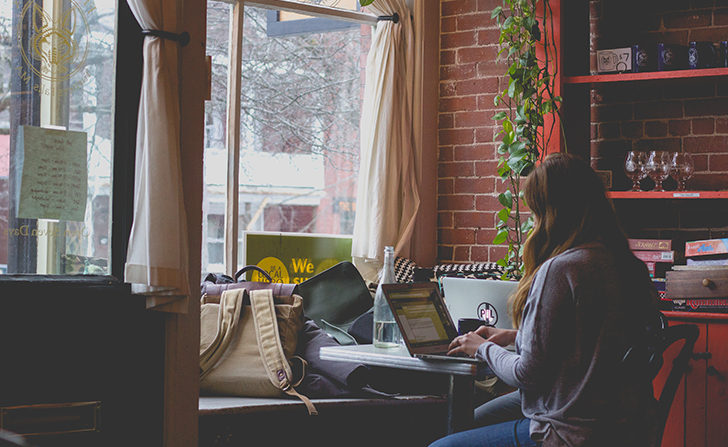 woman working on a laptop faces the window inside a coffee shop
