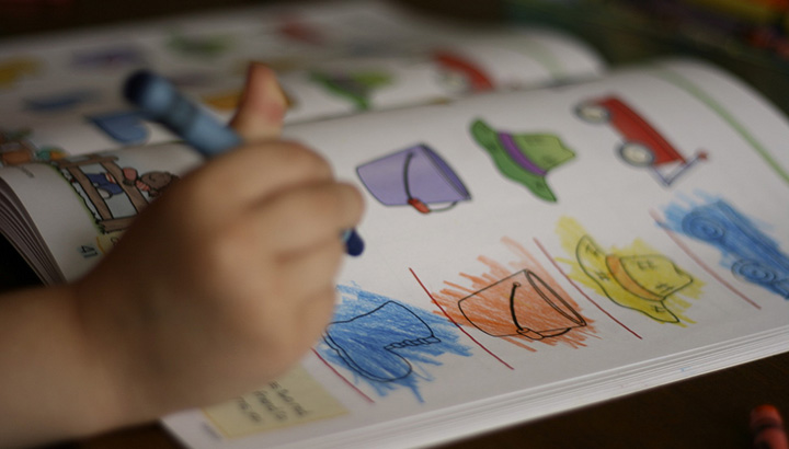 child's hand with a crayon coloring line images of hats in many colors