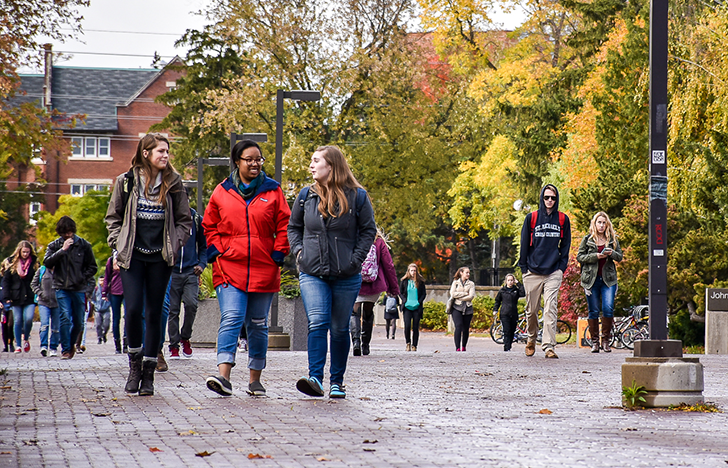 students walking along campus courtyard on a fall day