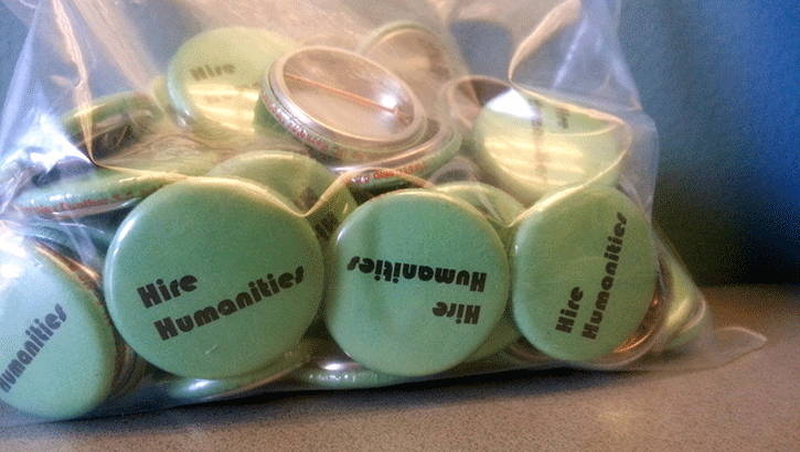 """Zip bag filled with yellow pins that read """"hire humanities"""""""