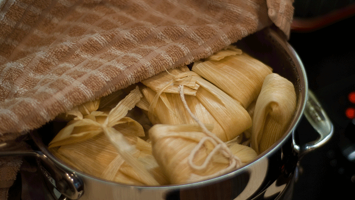A pot filled with roasted corn tamales