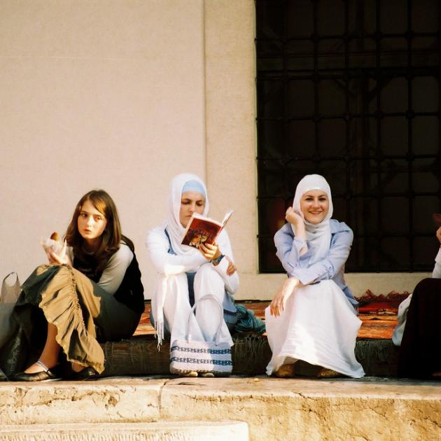 Five women sitting on stairs outside a building in Sarajevo chatting. Four are veiled, and one is reading a book.