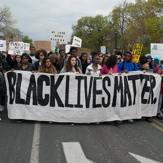 "Students march in protest with a large banner sign, ""Black Lives Matter"""