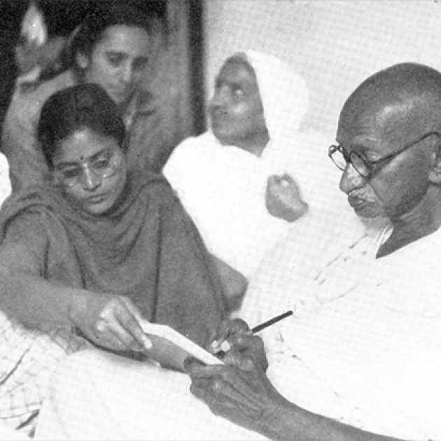 Gandhi seated, surrounded by people, writing a prayer message, January 18, 1948