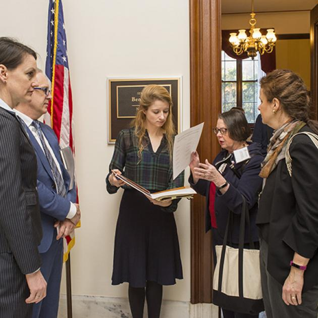 A group of five humanities advocates talk together outside an office door at the Capitol