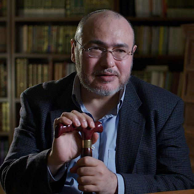 photo of Khaled Abou El Fadl sitting with a cane in front of a bookcase