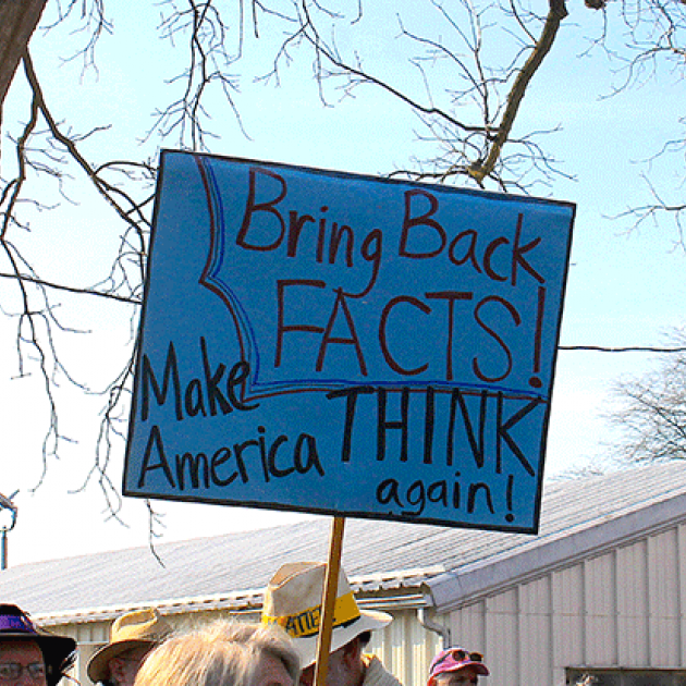 "A protest sign reads ""Bring Back Facts! Make America THINK again!"""