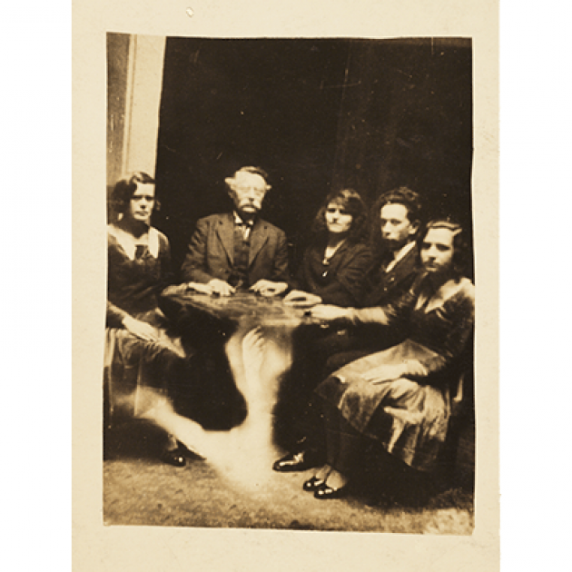 Black and white photograph of 2 men and 3 women around a table, each with one hand on top of it. A spectre of a hand arises from the floor toward the bottom of the table.