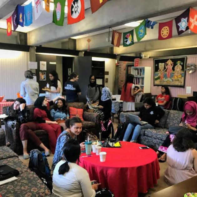 a group of yound adults sit on couches and around a table eating while celebrating Jummah. Flags with symbols of religious faiths are affixed to the ceiling