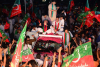 A car drives through a crowd of people waving the red and green flags of Pakistan's PTI political party. Then-PTI leader Imran Khan waves to the crowd from the car.